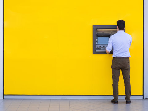Man withdrawing money from an atm bank machine
