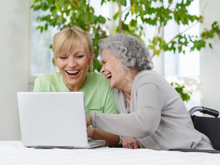 Pflegerin und Seniorin mit laptop