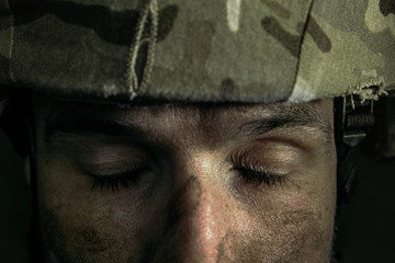 Empty eyes wanna be closed. Close up portrait of young male soldier. Man in military uniform on the war. Depressed and having problems with mental health and emotions, PTSD, rehabilitation.