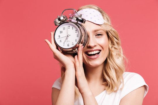 Portrait of attractive young woman 20s wearing sleeping mask holding alarm clock after awakening