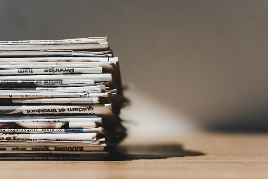 different print newspapers in pile on wooden table with shadow