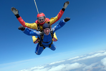 Skydiving. Tandem jump. Happy passenger and his instructor.
