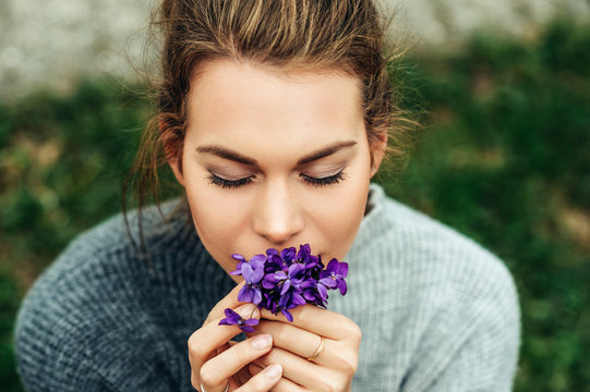 Spring portrait of pretty young woman wearing warm grey pullover, holding small bouquet of Woolly Blue Violet (Viola sororia)