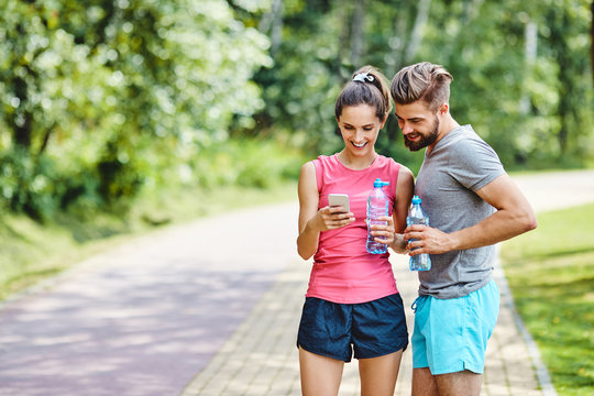 Two runners checking achievements on mobile phone app