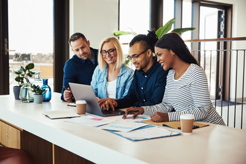 Smiling group of businesspeople working together at an office ta