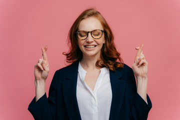 Photo of happy businesswoman crosses fingers for good luck, believes everything will be fine, prays over pink background, has toothy smile, wears spectacles and formal suit. Body language concept
