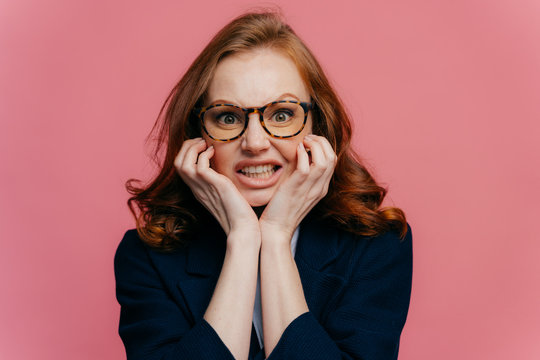 Negative feeling concept. Dissatisfied redhead prosperous businesswoman clenches teeth from irritation, keeps hands under chin, wears transparent glasses and black formal outfit, isolated on pink wall