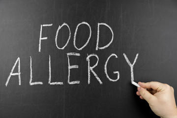 Allergy food concept. Hand with chalk writing on black chalkboard