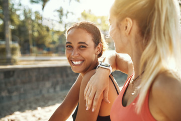 Wall Mural - Two laughing young women taking a break from exercising outside