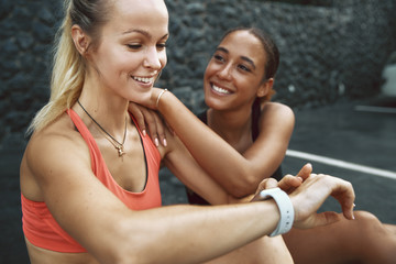 Wall Mural - Smiling woman checking her time after running with a friend