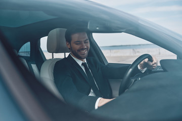 So happy! Handsome young man in full suit smiling while driving a car