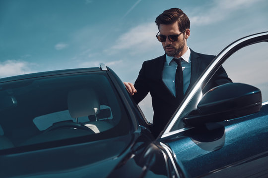 Time is money. Handsome young man entering his car while standing outdoors