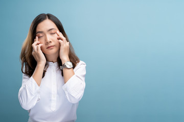 Woman has eyes pain isolated over blue background