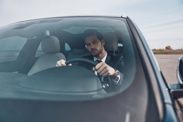 Careful driver. Handsome young man in full suit looking straight while driving a car