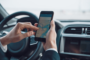 Checking the direction. Close up of young man using smart phone to check the map while driving a car
