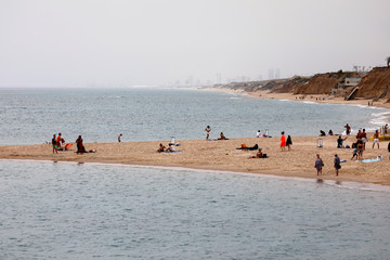 People visit a beach along the coast of the Mediterranean Sea in the southern Israeli city of Ashkelon