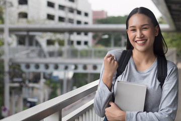 portrait of happy, smiling, successful, confident asian woman college student posing guts pose or fighting, add oil, success pose in city campus environment