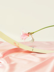 Artistic jewellery art with a pink flower on a metal curve