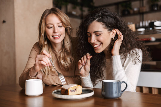 Excited happy pretty girls friends sitting in cafe drinking coffee eat cake.