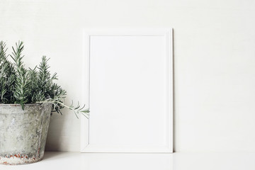 White vertical blank wooden frame mockup with rosemary herb in old metal flower pot on the table. Rustic summer poster product design. Gardening comcept. Styled stock feminine photography. Home decor.