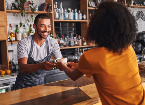 Male barista serves coffee cup to female customer in cafe