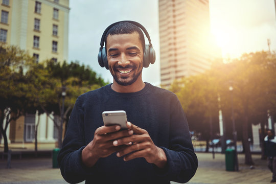 Young man looking at smartphone with headphone on his head