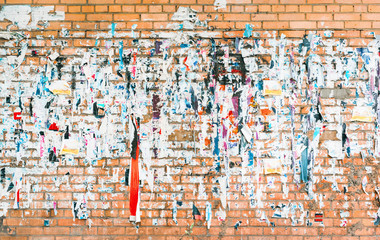 Brick wall with the remains of old advertisements and posters