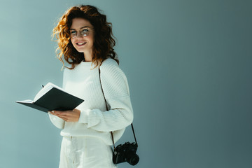 happy young woman with red hair holding notebook and pen while standing with digital camera on grey