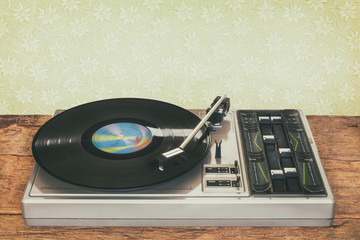 Old record player on a wooden table and retro wallpaper