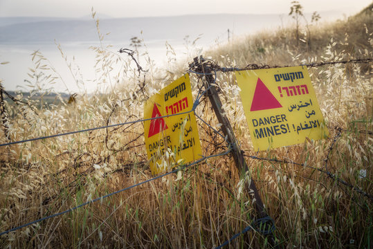 Yellow warning sign next to a mine field, close to the border with Syria, in the Golan Heights, Israel.