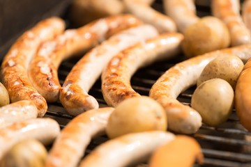 Delicious spicy sausages cooking on a grill