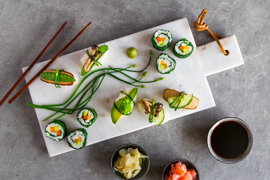 Vegan maki and nigiri sushi on white marble board over grey concrete background