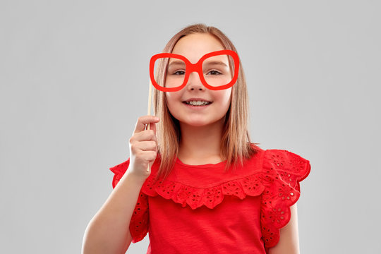 party props, photo booth and childhood concept - beautiful smiling girl in red shirt with big paper glasses over grey background