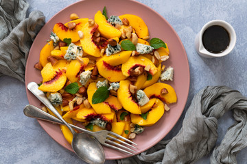 Peach salad with a fork and spoon to serve.