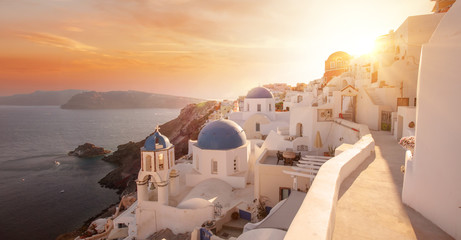 The famous three blue domes in Santorini at sunset Wall mural