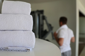Gym cleaning and hygiene concept. Stack of white clean towels