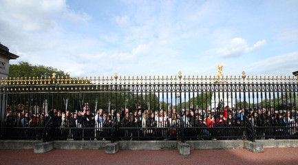 People take pictures of baby announcement easel in forecourt of Buckingham Palace, London
