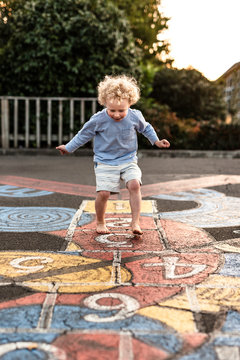 Happy toddler boy in mid-jump playing hopscotch