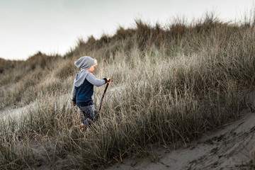 Boy with stick hiking up sand dune