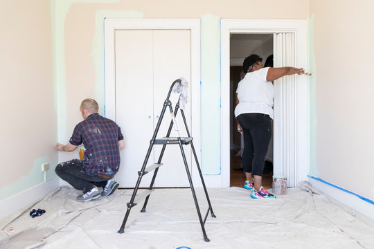 A young couple paint the bedroom of their new home.