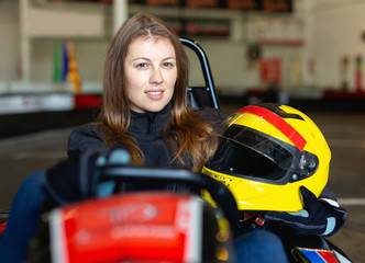 Young woman with helmet sitting in car for karting in sport club Wall mural