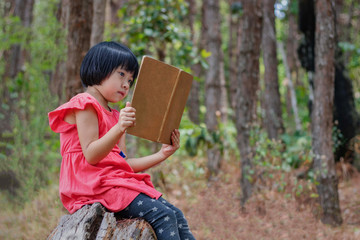 Asian girl is sitting reading a book on a timber in the forest.
