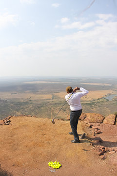 golfer playing 19th hole of a mountain cliff