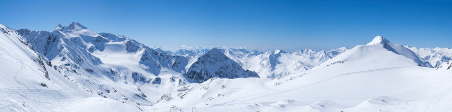 Panoramic landscape view from top of Schaufelspitze on winter landscape with snow covered mountain slopes and pistes at Stubai Gletscher ski resort at spring sunny day. Blue sky background. Stubaital