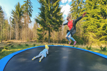 mother and daughter jumping on trampoline outdoors