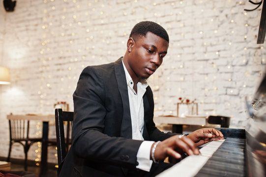 Strong powerful african american man in black suit play piano.