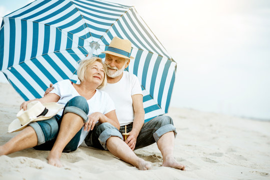 Happy senior couple relaxing, lying together under umbrella on the sandy beach, enjoying their retirement near the sea
