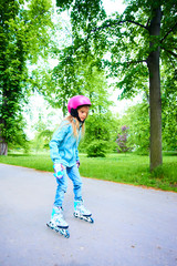 Cute little child girl learning to roller skate on beautiful summer day in a park. Child wearing safety helmet enjoying roller skating ride outdoors