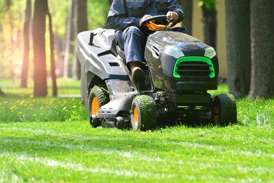 Professional lawn mower with worker cut the grass in a garden