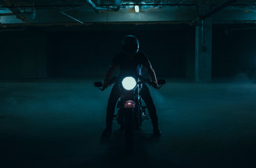 Silhouetted cafe racer motorcycle in a parking garage